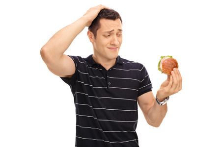 allurement: Tempted guy looking at a tasty sandwich isolated on white background