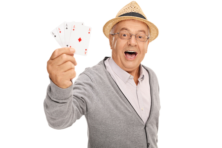 4 of a kind: Elderly man playing cards and showing four aces isolated on white background Stock Photo