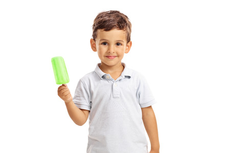child ice cream: Little kid holding a green ice pop and looking at the camera isolated on white background Stock Photo