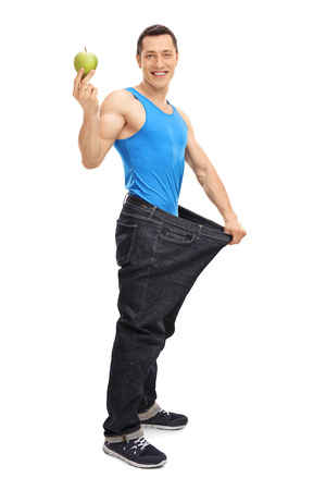 muscular men: Full length vertical shot of a guy in an oversized pair of jeans holding a green apple isolated on white background Stock Photo