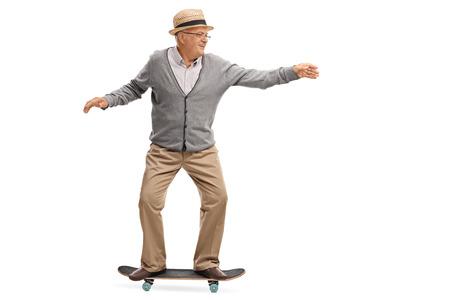 Joyful senior man riding a skateboard isolated on white background
