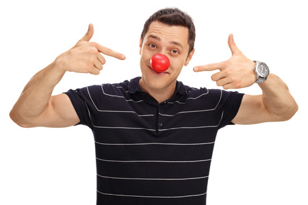 clown nose: Cheerful man pointing at his red clown nose isolated on white background