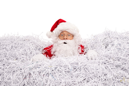 shredded paper: Confused Santa Claus drowning in a pile of shredded paper isolated on white background