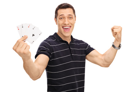 4 of a kind: Lucky young man holding four aces in his hand and gesturing happiness isolated on white background Stock Photo