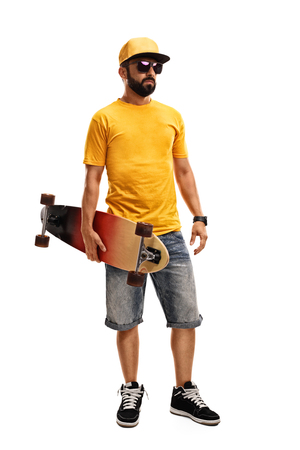 yellow shirt: Full length portrait of a cool man in a yellow shirt and cap holding a longboard isolated on white background Stock Photo
