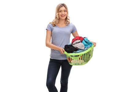 woman clothes: Cheerful woman holding a laundry basket full of clothes isolated on white background