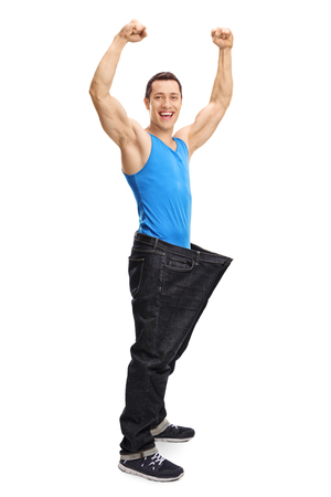 lose up: Full length portrait of a happy muscular man in a pair of oversized jeans isolated on white background Stock Photo
