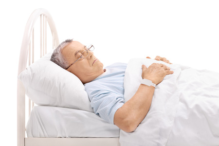 anticipating: Pensive mature patient laying on a hospital bed isolated on white background