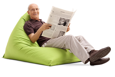 beanbag: Joyful senior holding a newspaper and sitting on a green beanbag isolated on white background