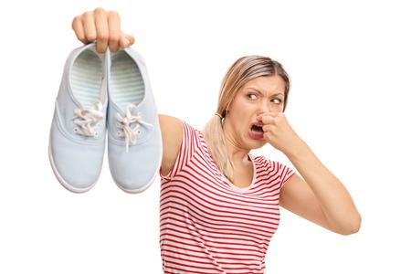 白い背景で隔離の臭い靴のペアを保持しているうんざりの女性 写真素材