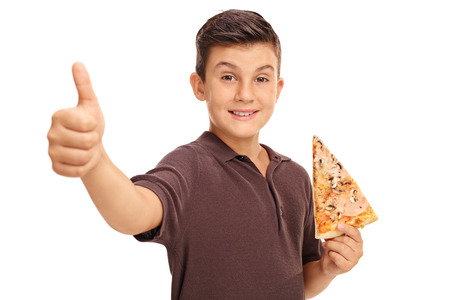 Happy boy giving a thumb up and holding a slice of pizza isolated on white background