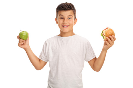 little one: Little boy holding an apple in one hand and a sandwich in the other isolated on white background
