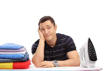 lame: Bored young guy sitting behind an ironing board and looking at the camera isolated on white background
