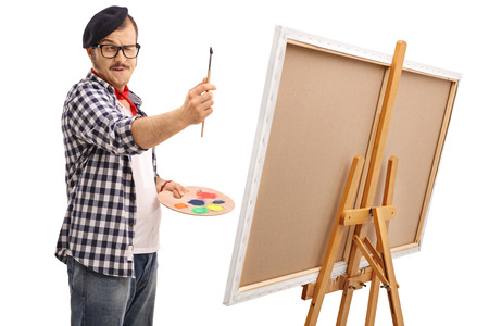 white canvas: Young artist measuring proportions with a paintbrush isolated on white background
