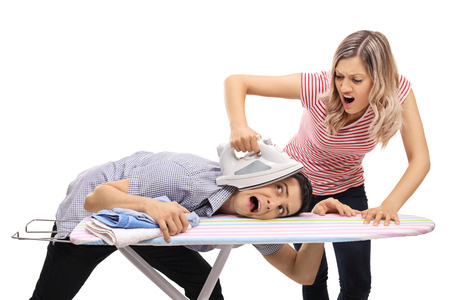 Angry young woman pressing the head of a man with an iron isolated on white background