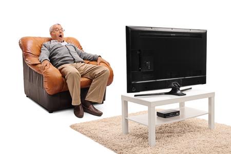 白い背景に分離された肘掛け椅子に座ってテレビで怖い映画を見て恐怖のシニア