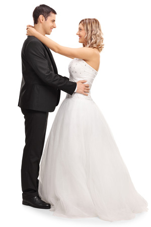 Full length portrait of a newlywed couple in love looking at each other isolated on white background