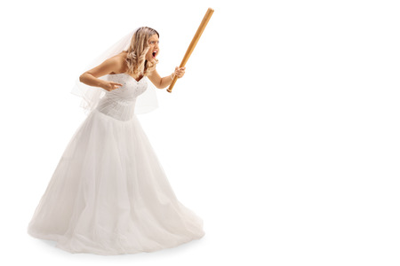 Full length portrait of an enraged bride threatening someone with baseball bat isolated on white background