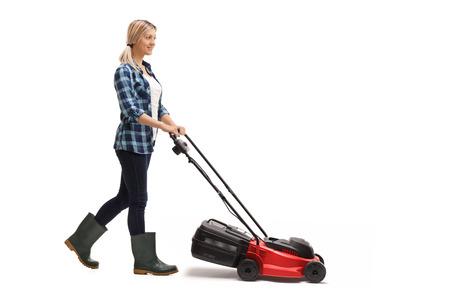행복 한 젊은 여자는 흰색 배경에 고립 된 잔디 깎는 기계를 밀고