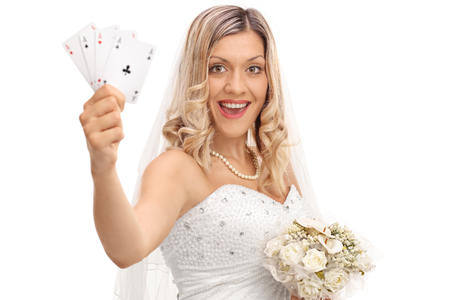 Joyful blond bride in a wedding dress holding four aces isolated on white background