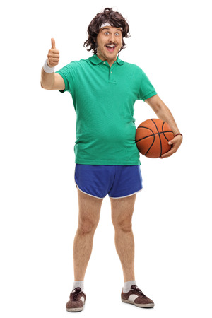 Full length portrait of a retro guy holding a basketball and giving thumb up isolated on white background