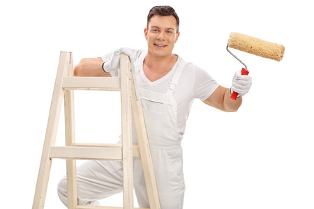 decorator: Studio shot of a cheerful young decorator holding a paint roller and standing on a ladder isolated on white background