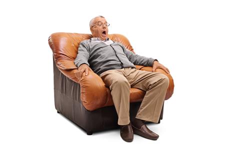 Scared Senior mit einem entsetzten Gesichtsausdruck sitzt auf einem Sessel auf weißem Hintergrund