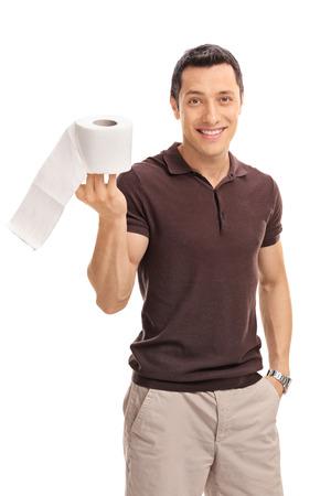 papel de baño: Tiro vertical de un chico joven alegre que sostiene un rollo de papel higiénico aislado en el fondo blanco