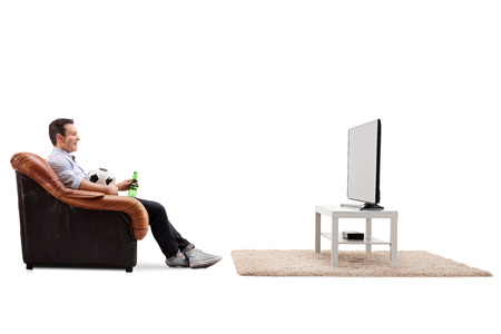 watching football: Profile shot of a joyful man sitting on an armchair and watching football on TV isolated on white background