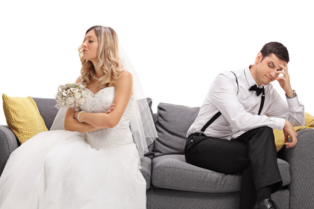 bride and groom background: Newlywed coupe sitting on a sofa angry at each other in a middle of an argument isolated on white background