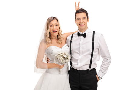 prank: Blond bride pulling a bunny ears prank on the groom on the wedding photo isolated on white background