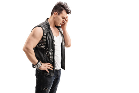baffled: Disappointed young punk rocker holding his head in disbelief isolated on white background