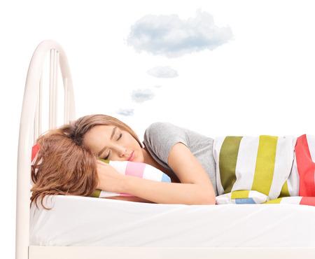 durmiendo: Brunette mujer durmiendo en una cama y soñando con una nube encima de la cabeza aislada en el fondo blanco