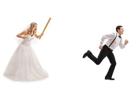 Angry bride chasing the groom with a baseball bat isolated on white background Stock Photo