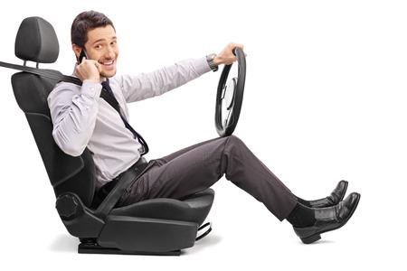 cinturon seguridad: Un joven sentado en un asiento del vehículo y hablando por teléfono celular aislado en el fondo blanco