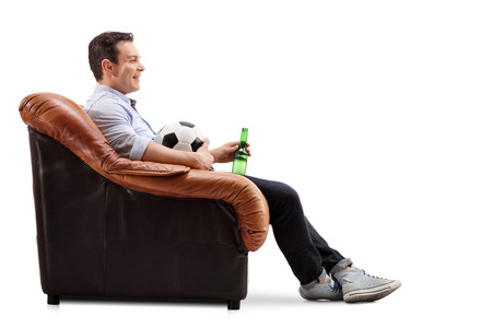 single beer: Young smiling adult sitting in an armchair holding a football and a beer in his hands isolated on white background