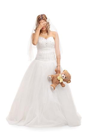 mujer sola: longitud completa tiro vertical de una joven novia triste que sostiene un oso de peluche aislado en el fondo blanco Foto de archivo
