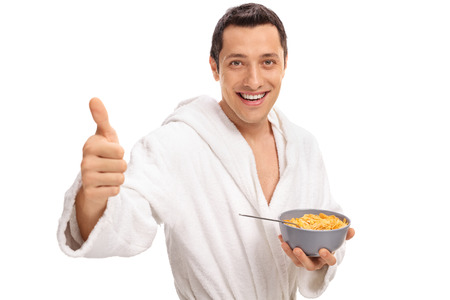 Cheerful young guy giving a thumb up and holding a bowl of cereal isolated on white background