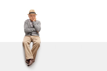 Depressed senior man sitting on a blank panel and contemplating isolated on white background Stockfoto