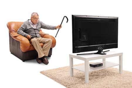 molesto: anciano enojado viendo algo molesto en la televisión aislado en el fondo blanco