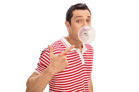Uomo allegro che mastica una gomma e che soffia una bolla isolata su fondo bianco