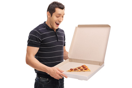 Delighted guy looking at a slice of pizza in a pizza box isolated on white background