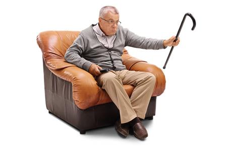 homme âgé Annoyed regarder la télévision assis sur un fauteuil isolé sur fond blanc
