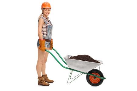 carretilla de mano: trabajadora joven posando con una carretilla llena de tierra aislada en el fondo blanco