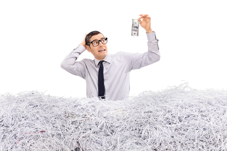 Worried businessman holding a dollar in a pile of shredded paper isolated on white background Stock Photo