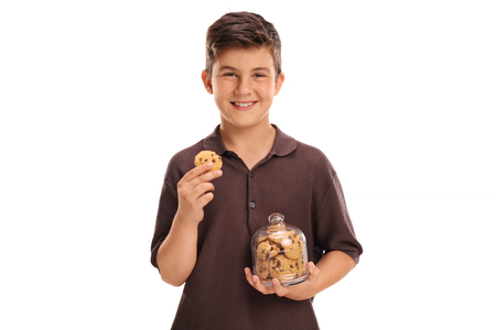 hold on: Cheerful child holding a cookie in one hand and a jar of cookies in the other isolated on white background