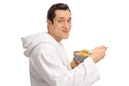 hombre comiendo: Perfil de disparo de un individuo joven que come el cereal de un recipiente aislado en el fondo blanco