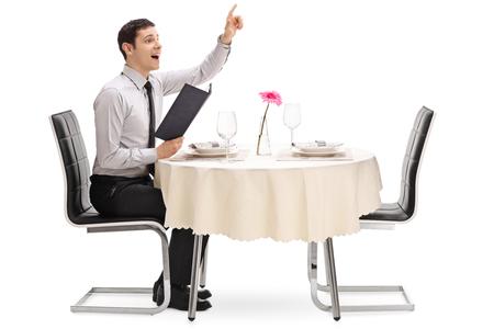 若い男、ウェイターを呼び出すと、白い背景で隔離のレストラン テーブルに座って