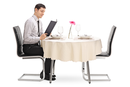 decide deciding: Young guy sitting at a restaurant table and reading the menu isolated on white background Stock Photo