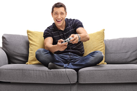 Cheerful young man seated on a sofa playing video games isolated on white background